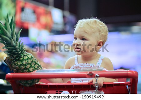 Adorable happy little baby girl in a beautiful dress sitting in red shopping cart in fruits and vegetables department at supermarket, she has chosen a big pineapple - stock photo