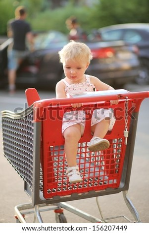 Adorable happy little baby girl in beautiful dress sitting in red shopping cart outside of a hypermarket on a parking lot; she enjoys warm summer day, sun is shining at her back - stock photo