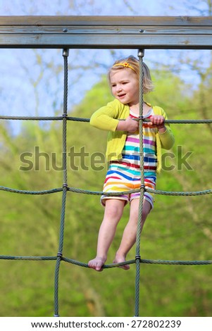 Adorable happy little child, blond sportive toddler girl, having fun outdoors climbing on playground in the park on a sunny spring or summer day - stock photo