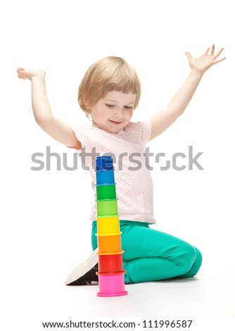 Adorable happy little girl building toy pyramid on white background