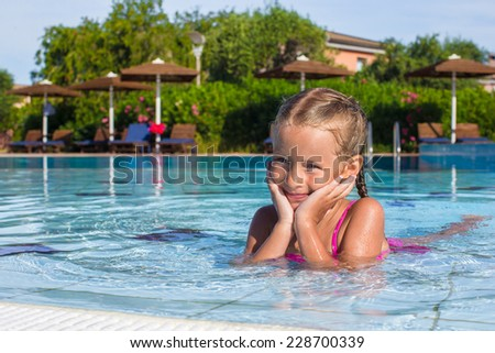 Adorable happy little girl enjoy swimming in the pool