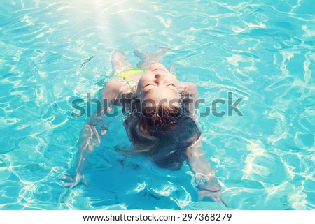 Adorable happy little girl enjoying time in the swimming pool