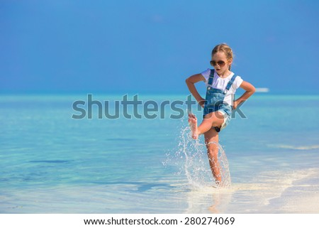 Adorable happy little girl have fun at shallow water on beach vacation - stock photo