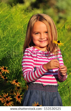 adorable happy little girl holding a Black Eyed Susan flower in the park - stock photo