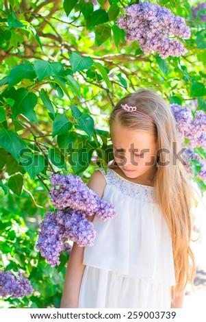 Adorable happy little girl in flower blossoming garden - stock photo