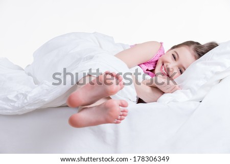 Adorable happy little girl in pink nightie awake in the bed on a white background. - stock photo