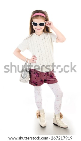 Adorable happy little girl in sunglasses posing with bag isolated on a white - stock photo