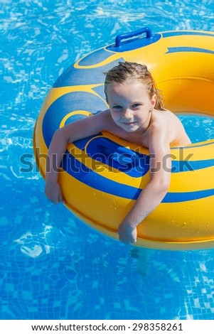 Adorable happy little girl playing in swimming pool