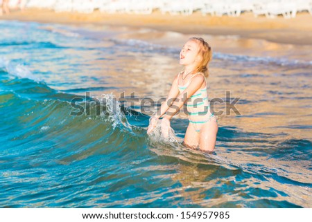 Adorable happy little girl playing in the sea on a beach - stock photo