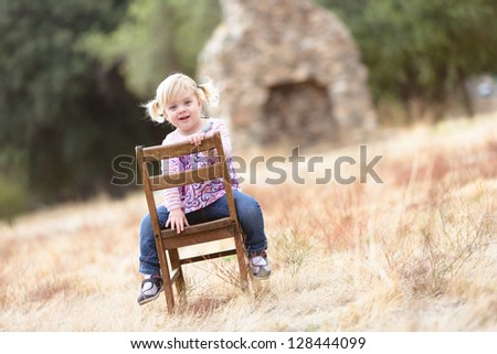 adorable happy toddler sitting in a field - stock photo