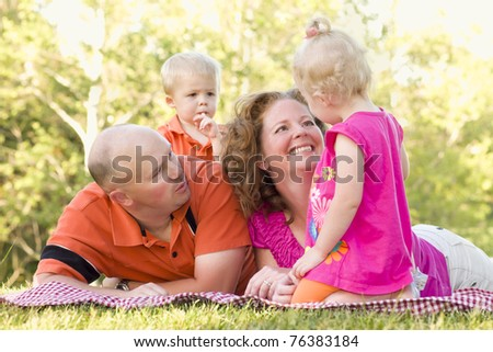 Adorable Happy Young Family with Cute Twins Enjoying a Day at the Park Together. - stock photo