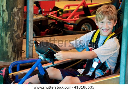 Adorable happy young kid on a go cart at an amusement park looking sideways. - stock photo