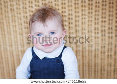 Adorable healthy baby boy looking at the camera and smiling, indoor. Portrait with copy space. - stock photo