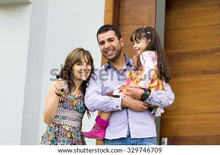 Adorable hispanic family of three posing for camera outside front entrance door. - stock photo