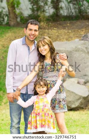 Adorable hispanic family of three posing in garden environment smiling happily to camera. - stock photo