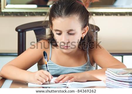Adorable hispanic girl studying at home - stock photo
