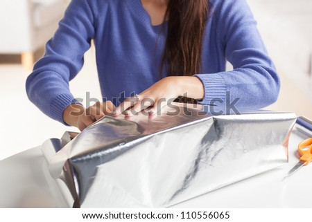 Adorable Hispanic woman wrapping gift with silver wrapping paper in living room at table wearing blue shirt. - stock photo