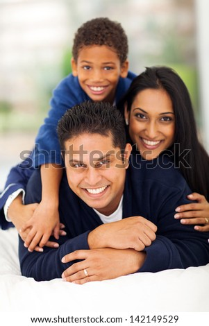 adorable indian family pyramid on bed at home - stock photo