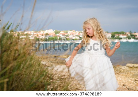 adorable innocent child with long hair in white dress - stock photo
