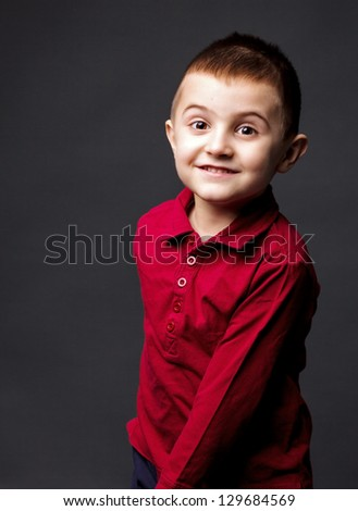 Adorable joyful little boy with funny expression on gray background - stock photo