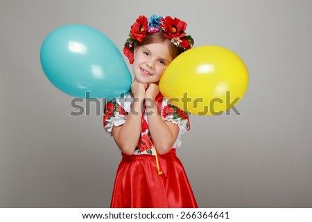 Adorable joyful little girl in Ukrainian national dress holding a yellow and blue air balloon and smiling/Ukrainian girl - stock photo