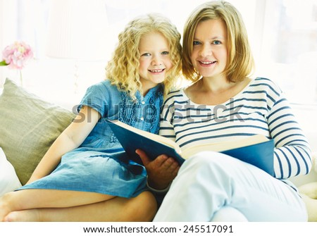 Adorable kid and her mother reading book at leisure - stock photo
