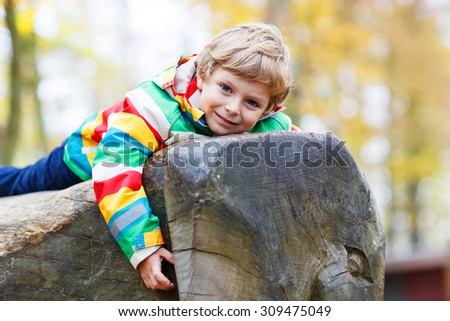 Adorable kid boy in colorful rain jacket with stripes and gumboots having fun with playing on playground on warm, autumn day, outdoors - stock photo