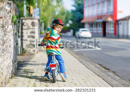 Adorable kid boy in red safety helmet and colorful raincoat riding his first bike on summer day. Active leisure for children outdoors. - stock photo