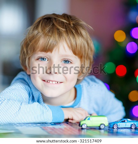 Adorable kid boy playing with cars and toys at home, indoor. funny child having fun with gifts. Colorful christmas lights on background. Family, holiday, kids lifestyle conceplt. - stock photo