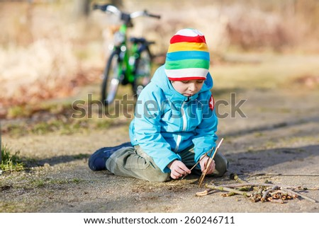 Adorable kid boy playing with wooden sticks in city park. Happy child in colorful clothes, spring or autumn. Creative games with kids outdoors in nature. - stock photo
