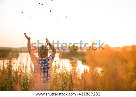 Adorable kid boy standing on a summer meadow with hands up. Sunset in the park. Outdoors. Vacations. Freedom and happiness. Child walking and enjoying nature. - stock photo