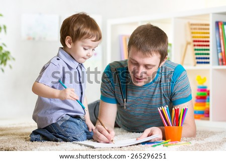 adorable kid child and his dad drawing with color pencils - stock photo