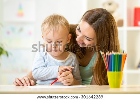 adorable kid child boy drawing with mother help - stock photo