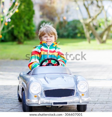 Adorable kid driving big toy old vintage car and having fun, outdoors. Active leisure with kids outdoors  on warm spring or autumn day. - stock photo