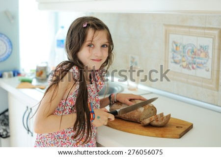 Adorable kid girl cuts bread on the kitchen with knife on wooden board - stock photo