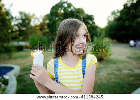 Adorable kid girl don't want to share ice cream. Family lifestyle - stock photo