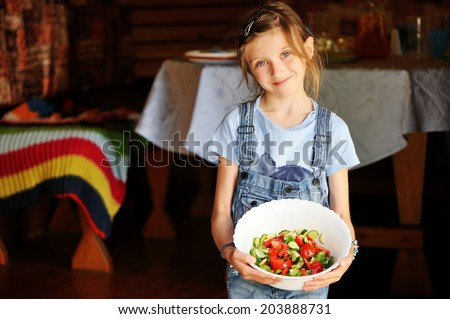 Adorable kid girl holding a bowl with homemade green salad with olive oil