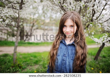 Adorable kid girl in blooming cherry garden on beautiful spring day - stock photo