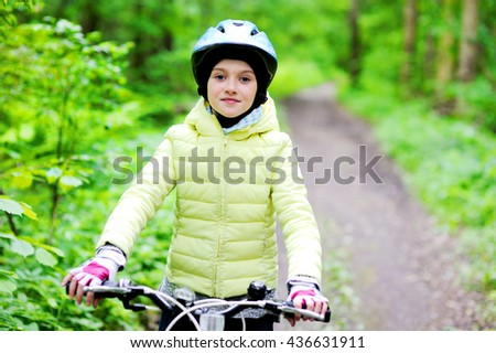 Adorable kid girl in blue helmet and jacket riding on bicycle in the forest - stock photo