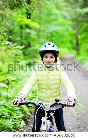 Adorable kid girl in blue helmet and jacket riding on bicycle in the forest