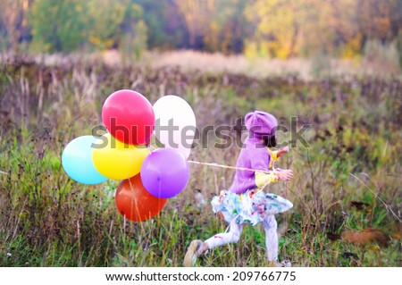 Adorable kid girl in colorful fashion outfit run  with bunch of colorful balloons in the field at the warm autumn day: focus on balloons - stock photo