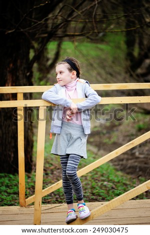 Adorable kid girl in grey outfit has fun in the spring park