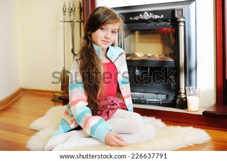 Adorable kid girl in in cozy warm sweater near fireplace - stock photo