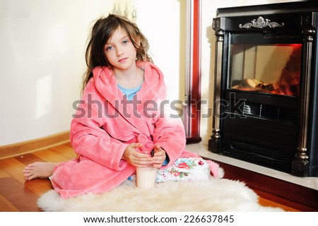 Adorable kid girl in pajama sitting near fireplace with glass of milk