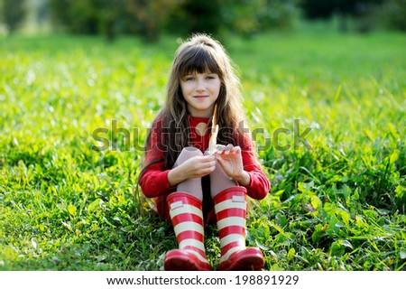 Adorable kid girl in red sweater dress and stripe rainboots having fun with bird feathers outdoors in the sunny autumn day