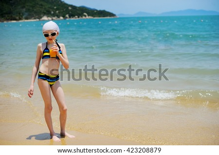 Adorable kid girl in swimsuit  drinking juice on the beach - stock photo