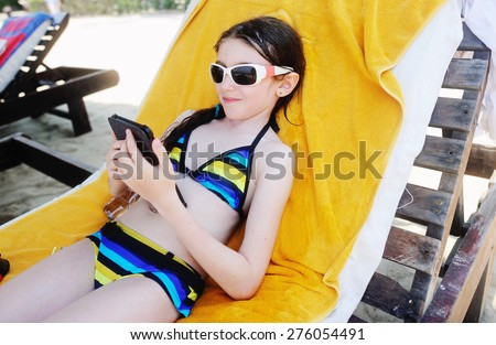Adorable kid girl reading a book on the beach - stock photo