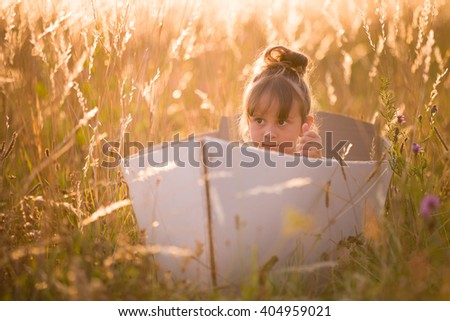 Adorable kid girl seaman floats on a handmade sailing boat in the field at sunset on a warm evening summer. Dreams of travel!  - stock photo