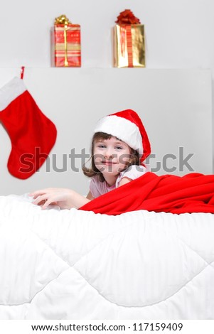 adorable kid girl sitting on her bed and holding a Christmas gift