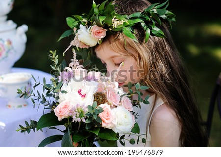 Adorable kid girl with bouquet in the garden - stock photo